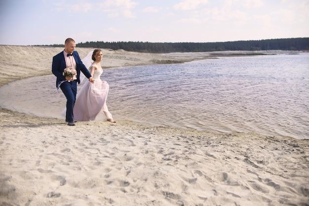 幸せな新郎新婦が海岸湖に沿って走る
