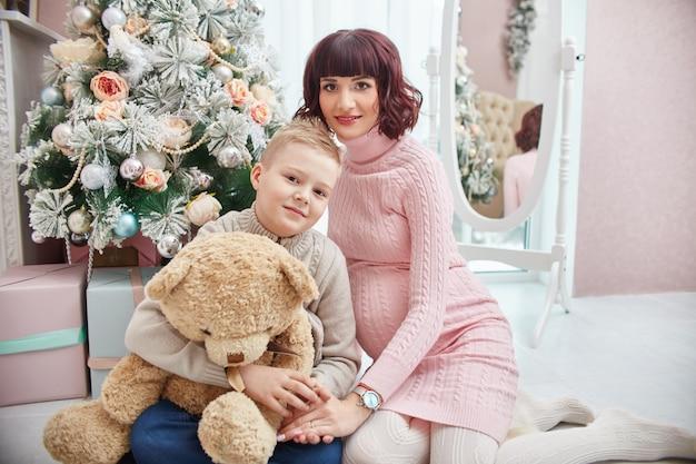 クリスマスツリーの横にポーズの息子と妊娠中の母親