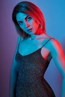ファッションポートレート少女光ネオンランプ青赤色。女性が色付きの背景、美しいメイクでポーズします。