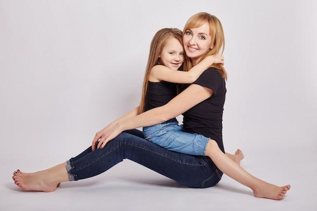 Мама и дочка обнимаются, сидя на полу. любящая семья.