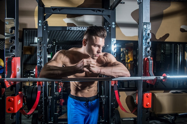 大きな筋肉とジム、フィットネス、腹部圧迫で腹筋運動の広いバックトレインを持つスポーティな男