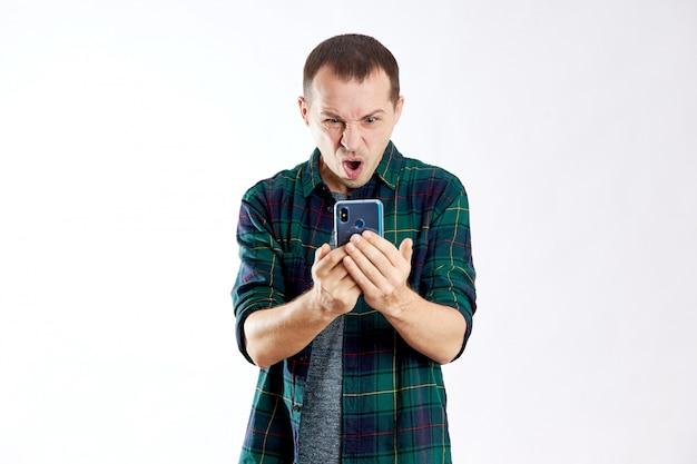 Парень держит телефон в руках и указывает на него пальцем. мужчина играет на своем телефоне и смотрит видео, в социальных сетях