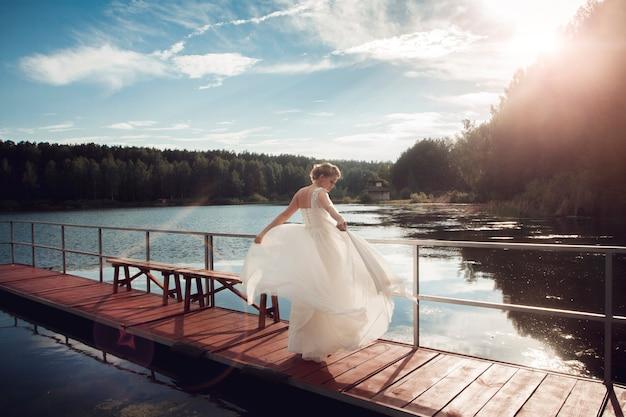 新郎新婦が湖の橋の上に立っています。夫婦。美しい結婚式のカップルのキスと湖の近くの橋でポーズ