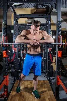 ダンベルのジムでセクシーな男。ジム、フィットネス、腹部の圧迫運動で、大きな筋肉と広い背中の筋肉を持つスポーティな男。