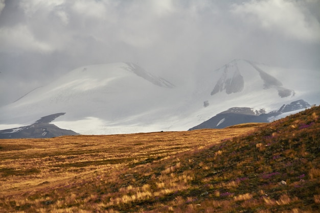 白い積雲の雲が山から降りてくる、草原の秋の風景。アルタイのウコク高原。素晴らしい寒い風景。誰でも