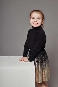 ホワイトキューブの上に座って、ポーズのカジュアルな服装で長い髪のファッションの女の子。美しい若い子。