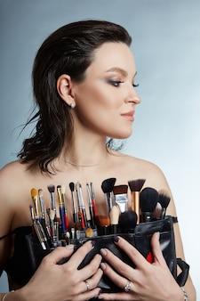 女性のメイクアップアーティストの美しさの肖像画。女の子の手に化粧ブラシ