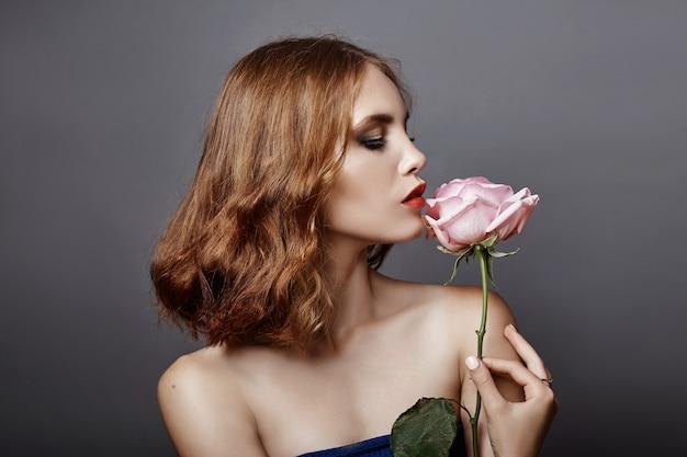 彼女の手に大きな花を持つ女性。素敵な女性