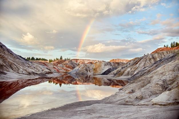 Закат с радугой в песчаных холмах. сказочный волшебный пейзаж. красивые разноцветные горы, озеро красного цвета