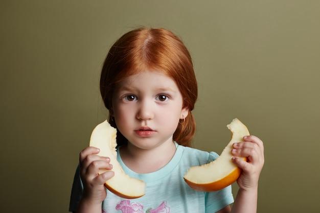 小さな女の子はメロンを食べる