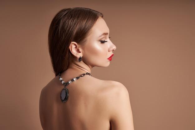 Портрет красоты женщины с ювелирными изделиями, серьгами в ее ушах и ожерельем вокруг ее шеи.