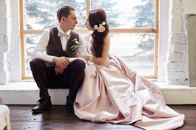 結婚式の前に抱き締める大きな窓の近くの新郎新婦。