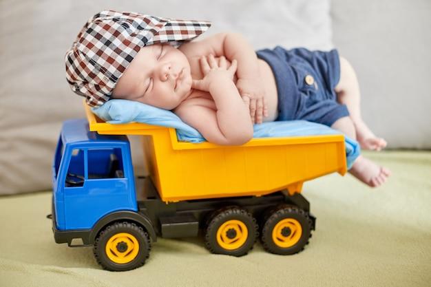 小さな新生児がおもちゃのトラックで寝ています。赤ちゃんの人生の最初の日、赤ちゃんの健康安全