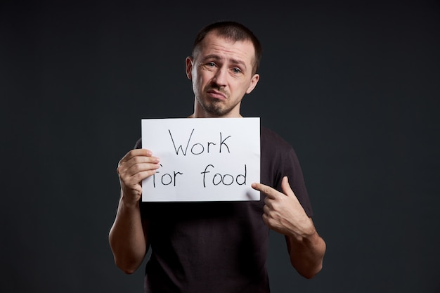 Мужчина держит в руках лист бумаги с надписью «я работаю за еду». улыбка и радость, место для текста, копия пространства