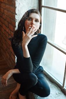 Женщина стоит у окна и курит сигарету.
