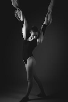 黒の背景にポーズをとって女性体操選手
