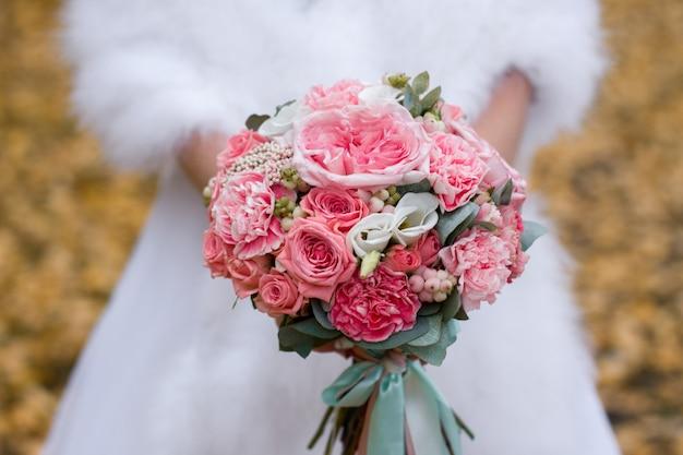 花嫁の手に花の花束。結婚式