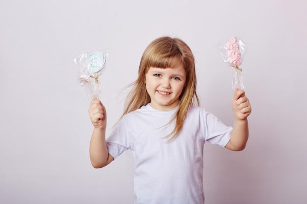 ブロンドの髪を持つ美しい少女は、ロリポップを食べる