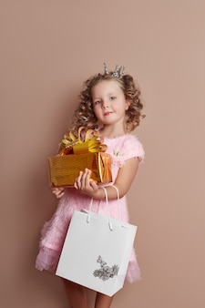 ピンクのドレスの少女は金のギフトボックスを保持します