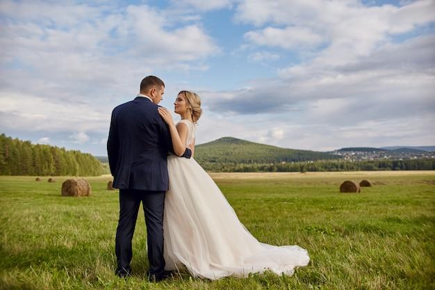 新婚夫婦は、フィールドで、結婚式を歩いてリラックス