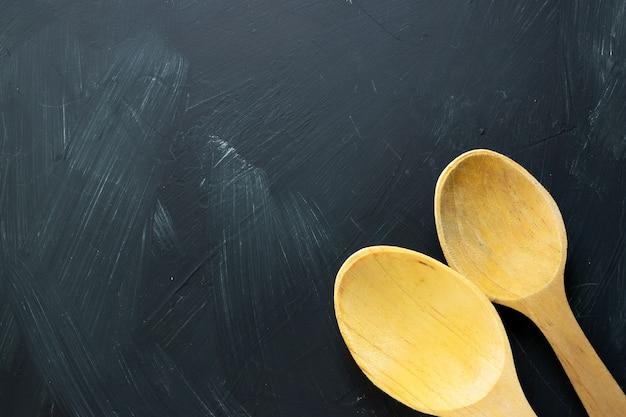 黒の織り目加工の背景を持つ木のスプーン