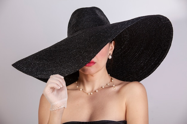 帽子、手袋、宝石類、赤い唇を持つ美しい女性。レトロファッション