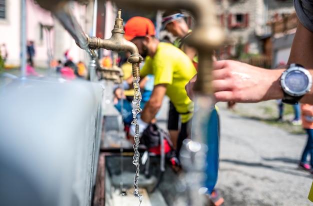 Утечка воды из крана и бегунов, заполняющих рюкзак в горной гонке