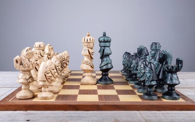 コレクションのピースが並んでいる王様が直面しているチェス盤