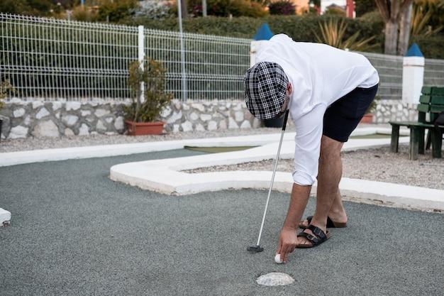 Мальчик кладет мяч для гольфа, чтобы бросить
