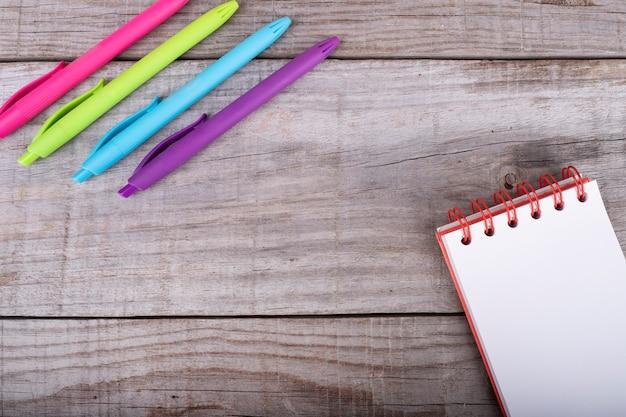 Блокнот с белыми листами и набор цветных ручек на деревянном фоне