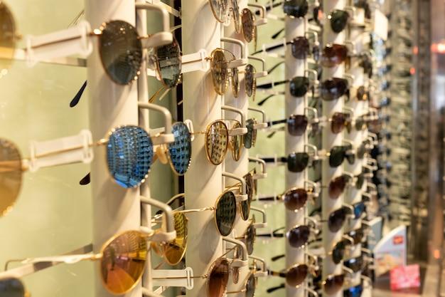 Солнцезащитные очки разных цветов в витрине для очков в оптике