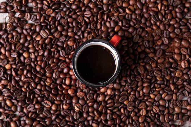 作りたてのコーヒーを中心に赤い金属製のカップとコーヒー豆