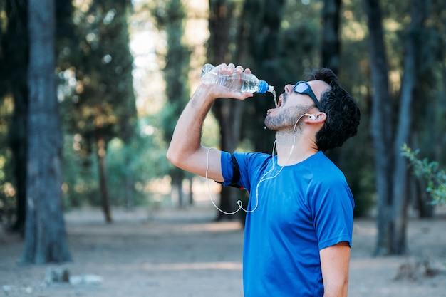 白人男性は水を飲むと運動しながら公園で音楽を聴きます。