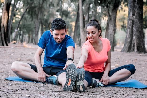 ストレッチ体操をしている公園に座っているカップル