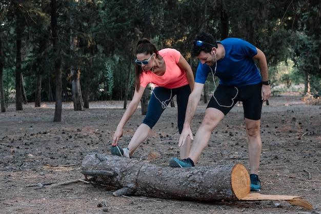 男と女の屋外ストレッチ体操を行う