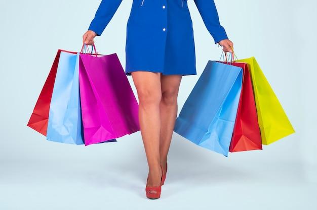 青いドレスと明るい青の背景にカラフルな分離ショッピングバッグを保持している赤い靴の女性の断面図画像。