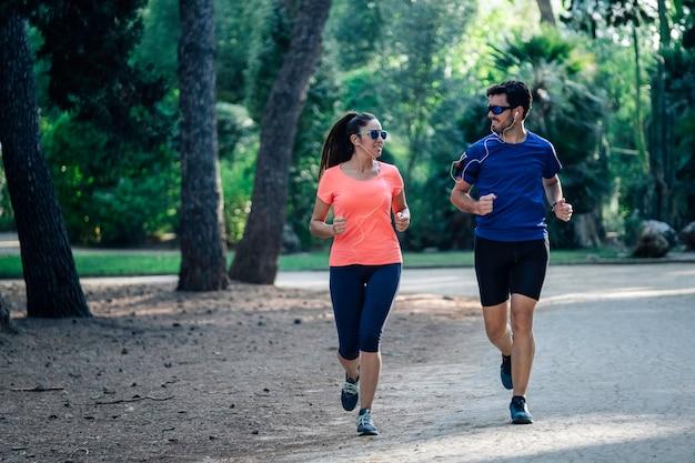 公園を通って実行し、音楽を聴く若いカップル。健康的な生活のコンセプト。