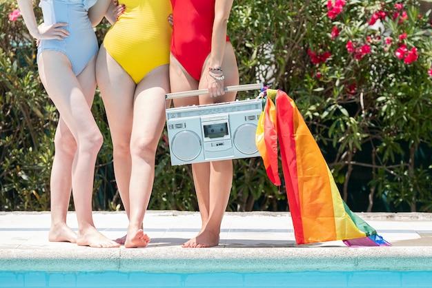古いレコードプレーヤーとプールで日光浴の友人のグループ