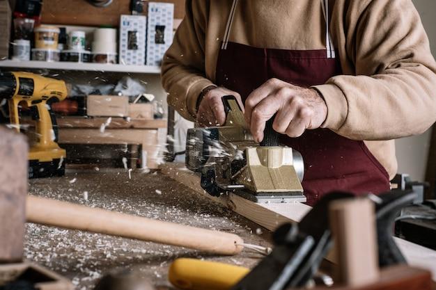 Плотник обрабатывает дерево электрической щеткой