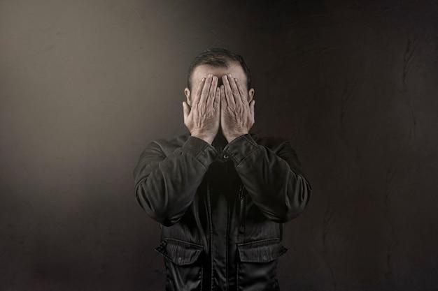 彼の手で彼の顔を隠す男