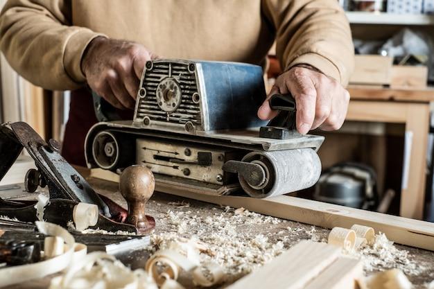 Электрический ленточный шлифовальный станок, шлифовальный станок в мужской руке. обработка заготовки на светло-коричневом деревянном столе. вид сбоку, крупным планом