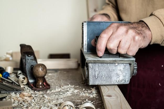 Электрический ленточный шлифовальный станок, мужской ручной шлифовальный станок. обработка заготовок на светло-коричневом деревянном столе. передний план