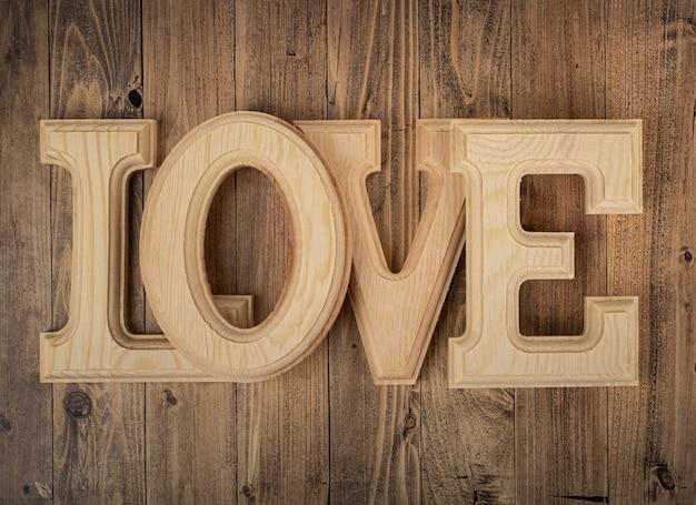 クルミの木のテーブルに愛という言葉を形成する木製の手紙。聖バレンタインの日の概念