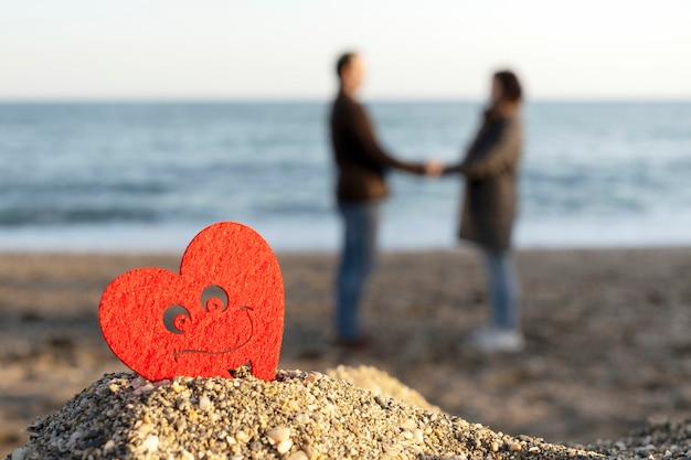 恋人のカップルと海沿いの砂の山に赤いハート。サンバレンタインの概念