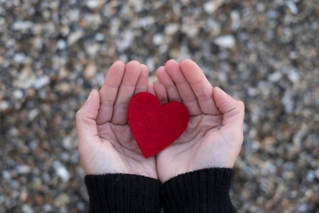 ビーチの石の女性の手の間の赤いハート。サンバレンタインの概念