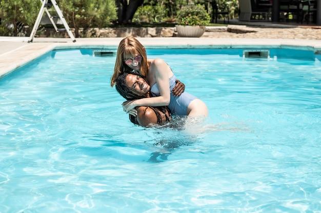 Афро-американский мужчина и белая женщина играет в бассейне.