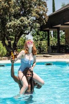アフリカ系アメリカ人の男とプールで遊ぶ白人女性。