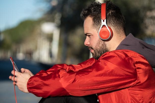 ヘッドフォンのペアで音楽を聴くスポーツウェアの若い男