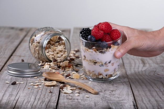 ヨーグルトと健康的な朝食のコンセプトの森の果物と穀物のガラスを持っている手