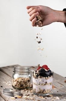 グラスにヨーグルトと森の果物と穀物を投げている手。健康的な朝食のコンセプト
